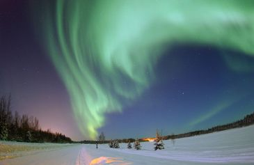 The_Aurora_Borealis_or_Northern_Lights_shines_above_Bear_Lake_at_Eielson_Air_Force_Base,_Alaska,_on_18_Jan_050118-F-MS415-003